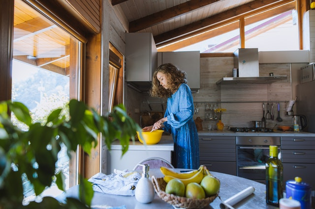a woman cooking after a kitchen remodel